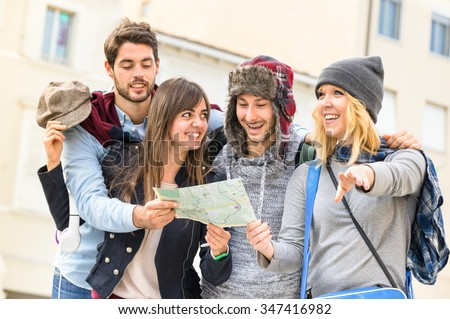 Group of young hipster tourists friends cheering with city map in the old town - Travel lifestyle concept with happy people having fun together - Winter fashion clothing wears with neutral color tones - stock photo