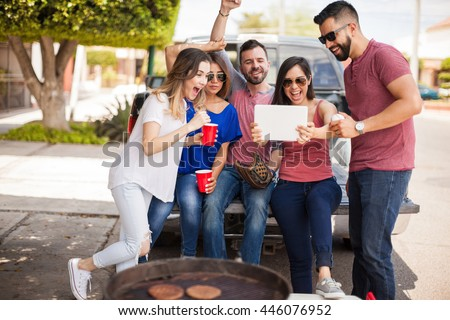 Group of young Hispanic friends tailgating and watching a baseball game on the back of a pick up truck with a tablet computer and supporting their team