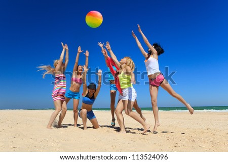 Group of young joyful girls playing volleyball on the beach - stock photo