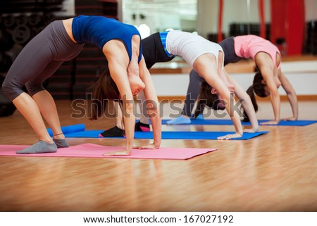 Group of young Latin women warming up and stretching at their yoga class - stock photo