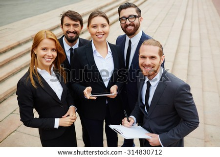 Group of young managers in formalwear looking at camera outdoors - stock photo