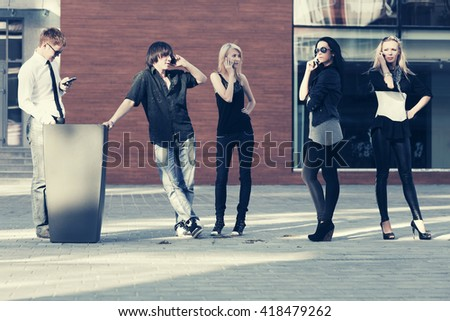 Group of young men and women calling on mobile phones outdoor. Male and female fashion model on city street - stock photo