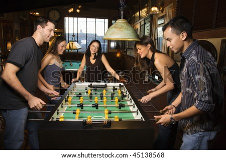 Group of young men and women enjoying a game of foosball in a bar.  Horizontal shot.