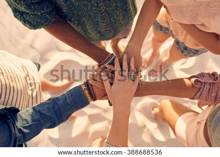 Group of young men and women showing unity. Group of young friends putting their hands together at the beach. - stock photo