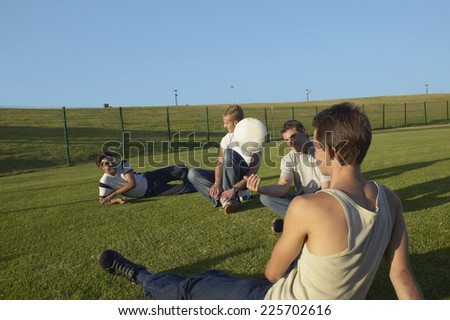 Group of young men relaxing in a field after playing soccer - stock photo