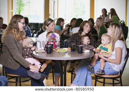 Group Of Young Mothers Relaxing In Cafe - stock photo