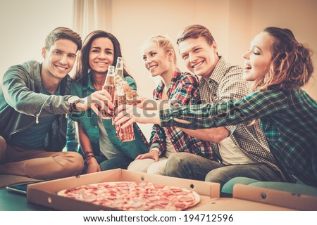 Group of young multi-ethnic friends with pizza and bottles of drink celebrating in home interior - stock photo