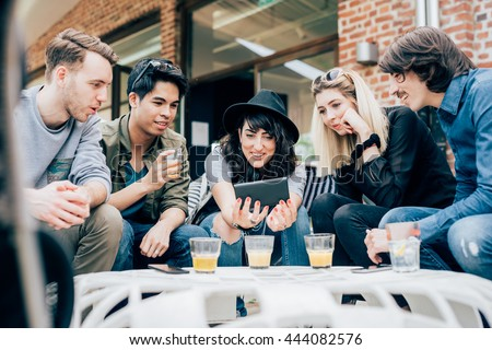Group of young multiethnic friends sitting in a bar having a drink, talking to each other holding a smart phone, having fun - happy hour, friendship, relax concept