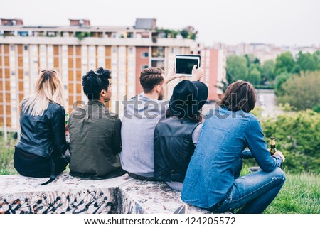 Group of young multiethnic friends sitting in a park, seen from behind, looking at the horizon taking selfie - future, prospective, friendship concept - stock photo