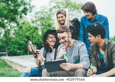 Group of young multiethnic friends sitting outdoor in the city, having a beer, chatting and using tablet handhold - friendship, relax, technology concept - stock photo