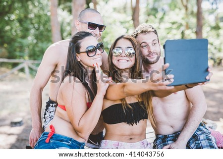 group of young multiethnic friends women and men at the beach  in summertime using tablet taking selfie - social network, technology, relax concept