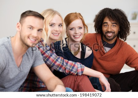 Group of young multiracial friends relaxing together sitting in a row on a sofa turning to smile at the camera - stock photo