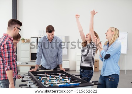 Group of Young Office Workers Enjoying Table Soccer Game Inside the Office During their Break time. - stock photo
