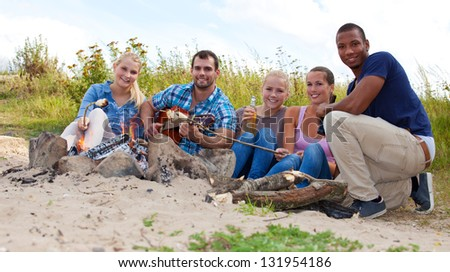Group of young people around camp fire. - stock photo