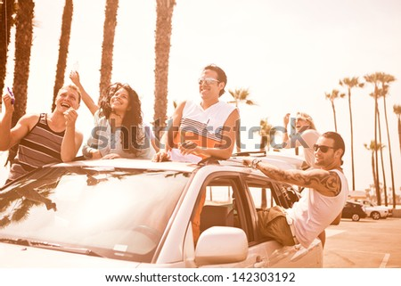 Group of Young People at Venice Beach in Los Angeles flying a Kite from a car - stock photo