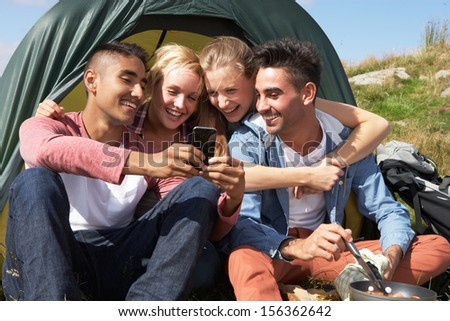 Group Of Young People Checking Mobile Phone On Camping Trip - stock photo