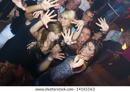 group of young people dancing and enjoying inside a night club - stock photo