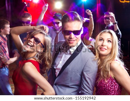 Group of young people dancing at the disco club - stock photo