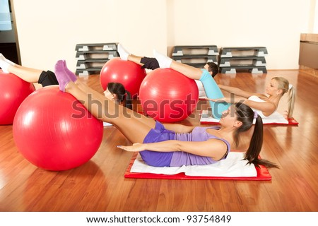 group of young people doing exercises with fitness ball - stock photo