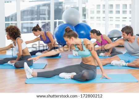Group of young people doing stretching exercises in the fitness studio - stock photo