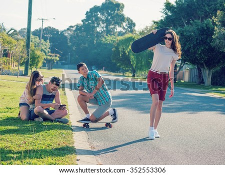Group of young people having fun together outdoors  in evening light with retro vintage old instagram style toned - stock photo