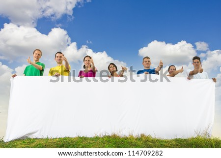 Group of young people holding a big blank paper in nature - stock photo