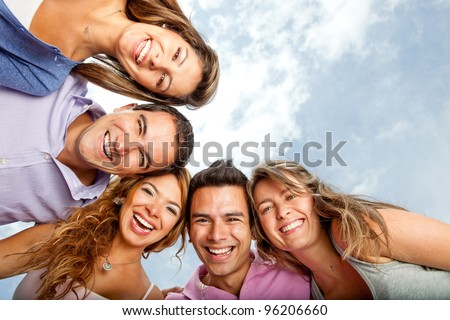 Group of young people hugging and laughing - stock photo