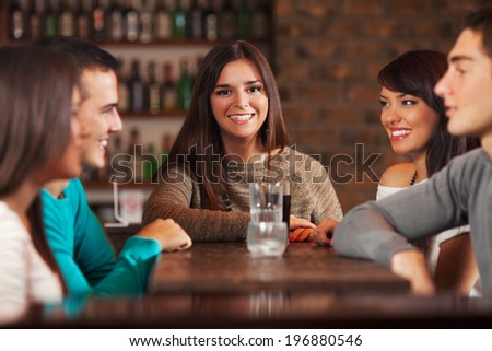 Group of young people in a bar. - stock photo