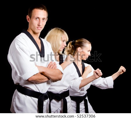Group of young people in kimono making martial arts exercise over black background. - stock photo