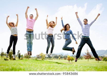 Group of young people jumping at the park - stock photo