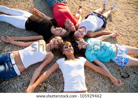 group of young people lie on the beach holding hands enjoying relax - stock photo