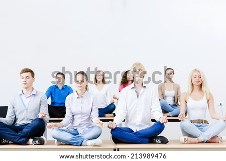 group of young people meditating on table in classroom - stock photo