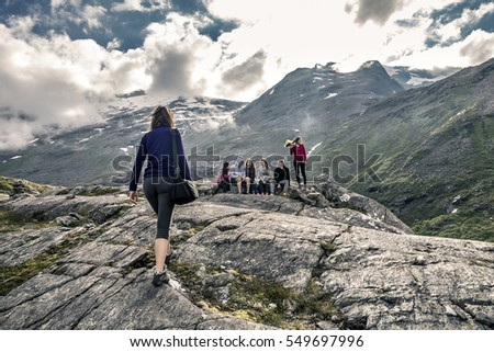 Group of young people on the top of mountain enjoying the beautiful view, Norway