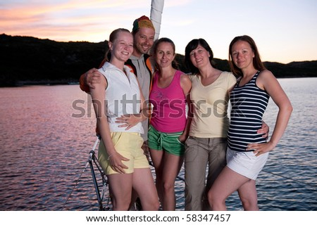 group of young people on the yacht during vacation with beautiful sunset in the background - stock photo