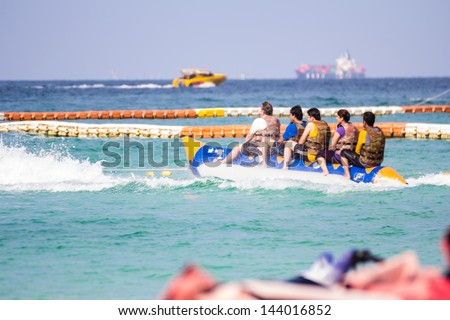 Group of young people riding banana boat - stock photo