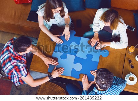 Group of young people sitting at a cafe, holding a puzzle pieces, top view - stock photo