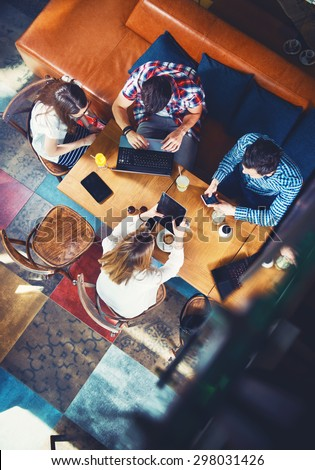 Group of young people sitting at a cafe, with mobiles and tablets, top view - stock photo