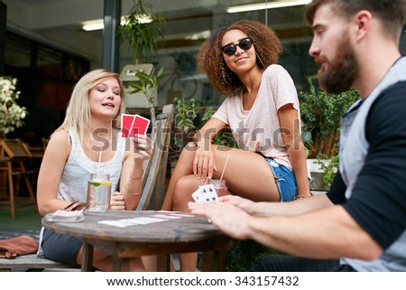 Group of young people sitting at the table and playing cards. Friends playing card game while sitting at outdoor cafe. - stock photo