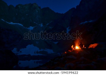 Group of young people sitting by the fire in mountains during dark night