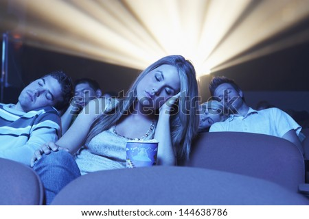 Group of young people sleeping while watching movie in the theatre - stock photo