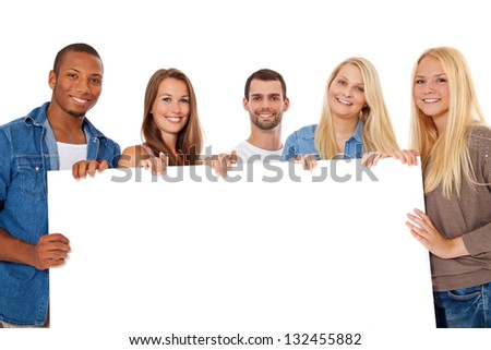 Group of young people standing behind white placeholder. All on white background. - stock photo