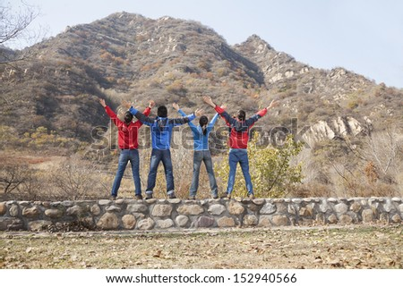 Group of young people standing on the ledge, arms outstretched - stock photo