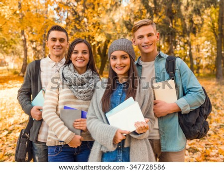 Group of young people students while walking autumn park - stock photo