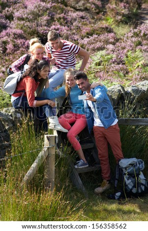 Group Of Young People Taking Photograph On Hike - stock photo