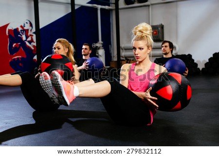Group of young people training with exercise ball at gym - stock photo