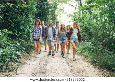 group of young people walking in the woods