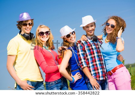 group of young people wearing sunglasses and hat - stock photo