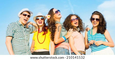 group of young people wearing sunglasses and hats hugging and standing in a row, spending time with friends - stock photo
