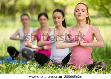 Group of young pregnant women doing relaxation exercise on exercising mat. - stock photo