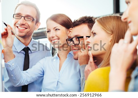 Group of young professional salespeople looking at a board with their results - stock photo